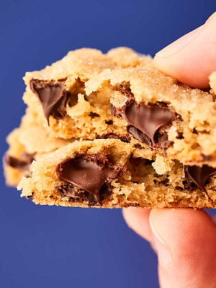 2 chocolate chip cookies with bites out, stacked, held