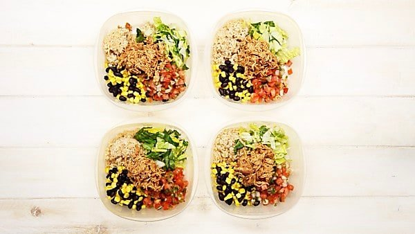 four assembled chicken burrito bowls