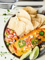 Chicken enchilada on plate with chips, lime, and pico above