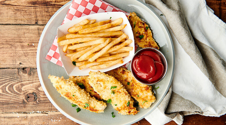 Chicken tenders on plate with fries and ketchup above