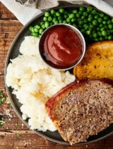 Plate of meatloaf, mashed potatoes, ketchup, peas, and texas toast above