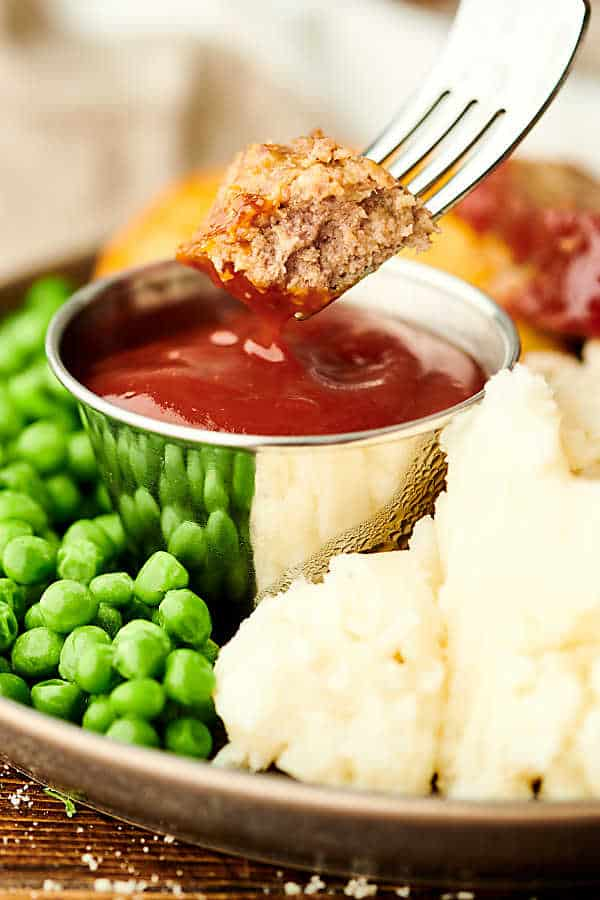 Piece of meatloaf being dipped into ketchup