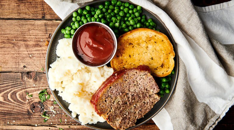 Plate of meatloaf, mashed potatoes, texas toast, peas, and ketchup above
