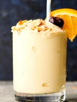 Cup of tropical smoothie with toasted coconut, cherry, straw, and orange slice