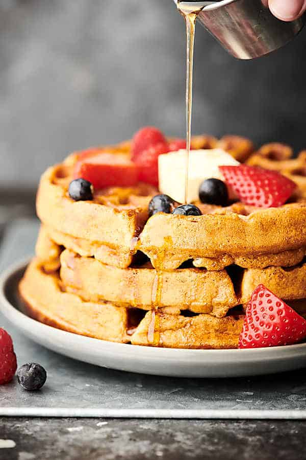 3 waffles stacked with blueberries, strawberries, butter, and maple syrup being drizzled