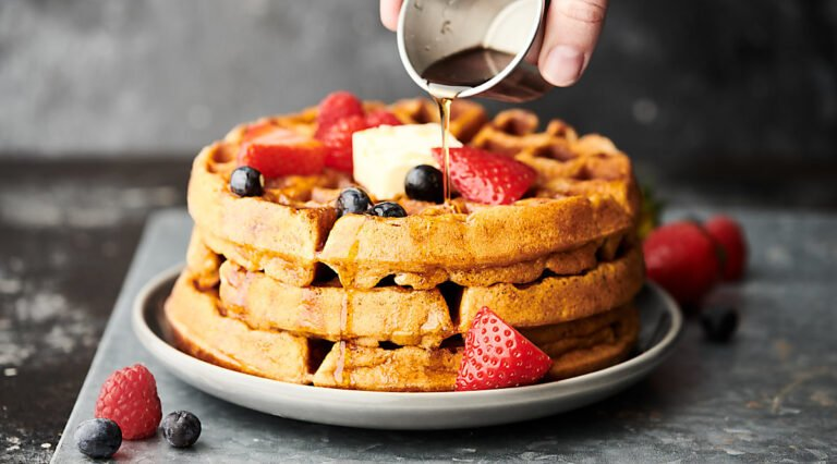 3 waffles stacked, topped with mixed berries, whipped cream, and being drizzled with maple syrup