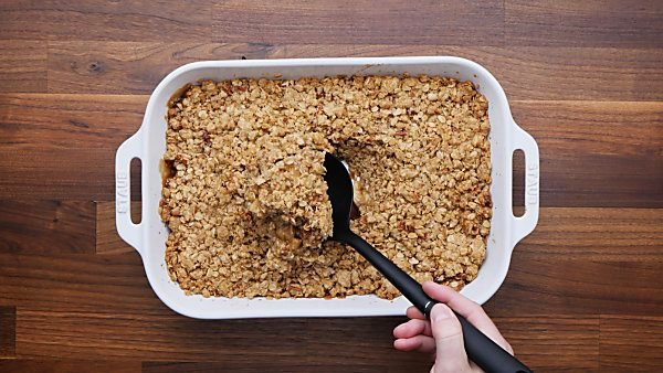 Baked apple crisp with ladle being scooped out