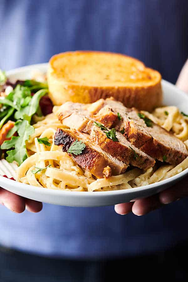 plate of chicken alfredo with side salad and garlic bread held two hands