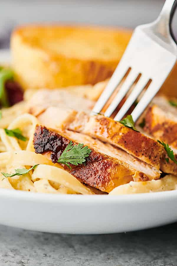 fork in plate of chicken alfredo