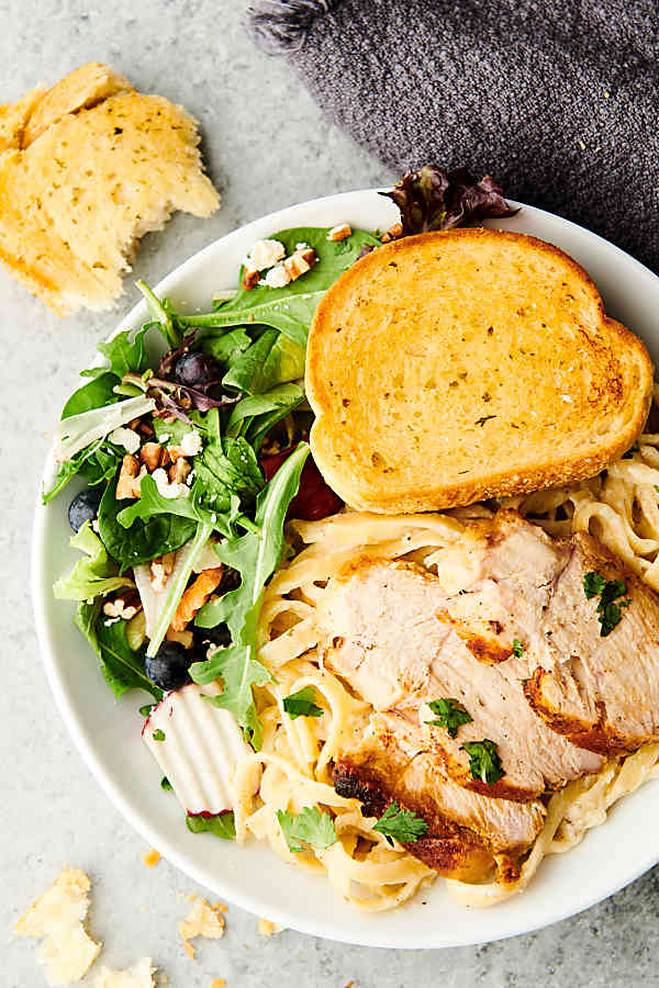plate of chicken alfredo with side salad and garlic bread above
