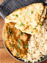 Chicken curry on a plate with naan and rice above