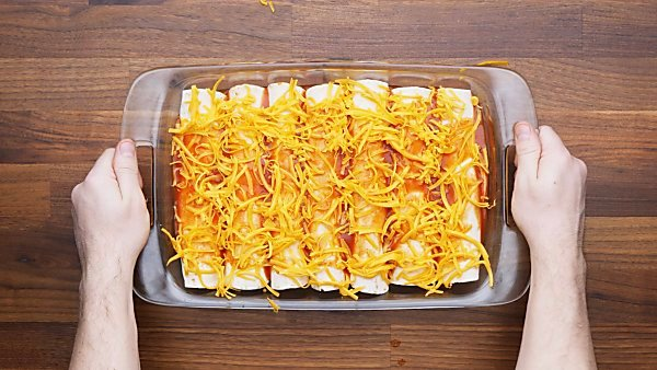 unbaked enchiladas topped with sauce and cheese