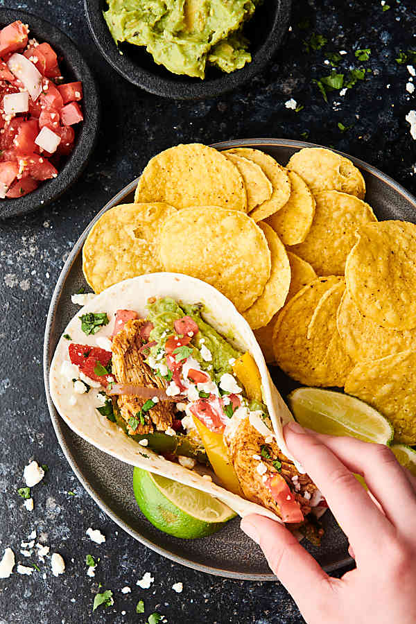 chicken fajita being set on plate with tortilla chips above