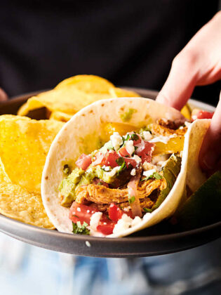 chicken fajita being picked up offplate with tortilla chips