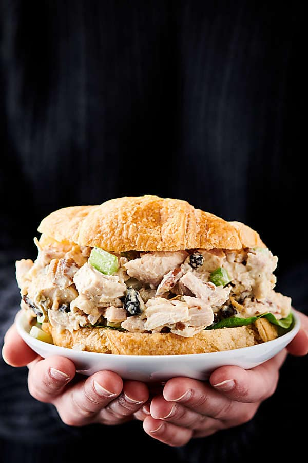 Chicken salad on a plate held in two hands