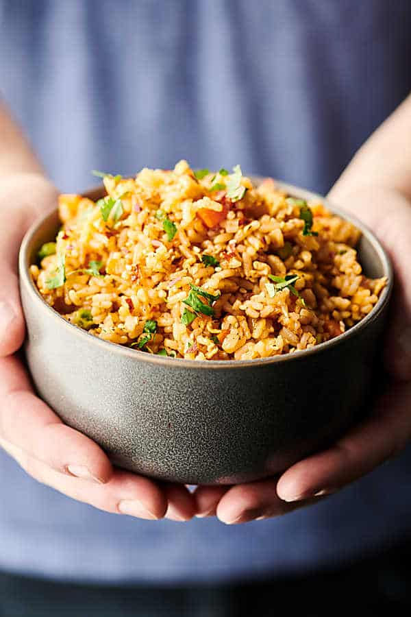 Bowl of fried rice held in two hands