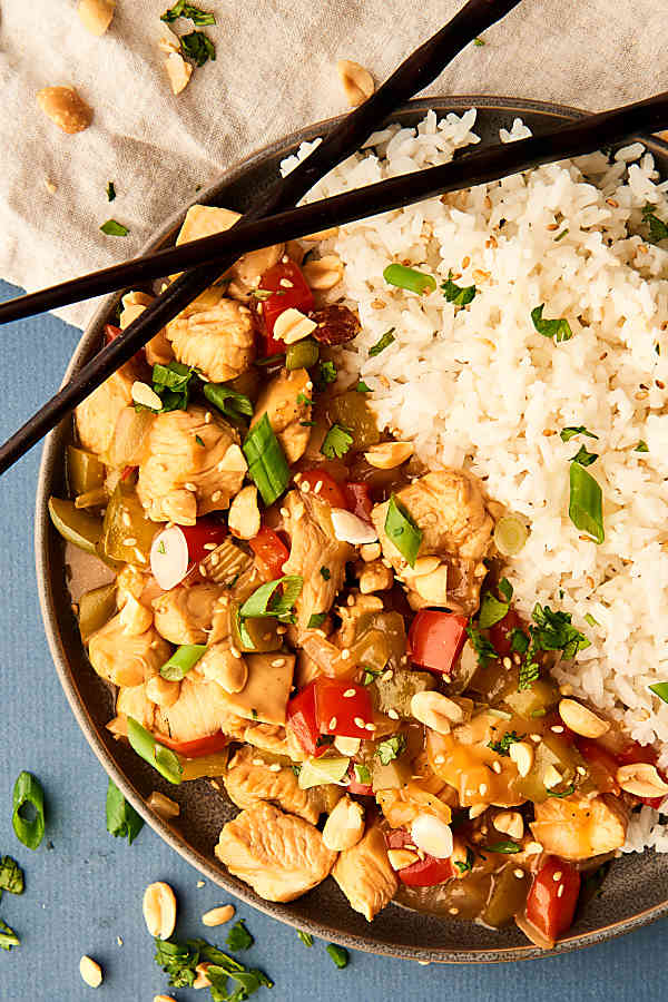 plate of kung pao chicken and rice with chopsticks above