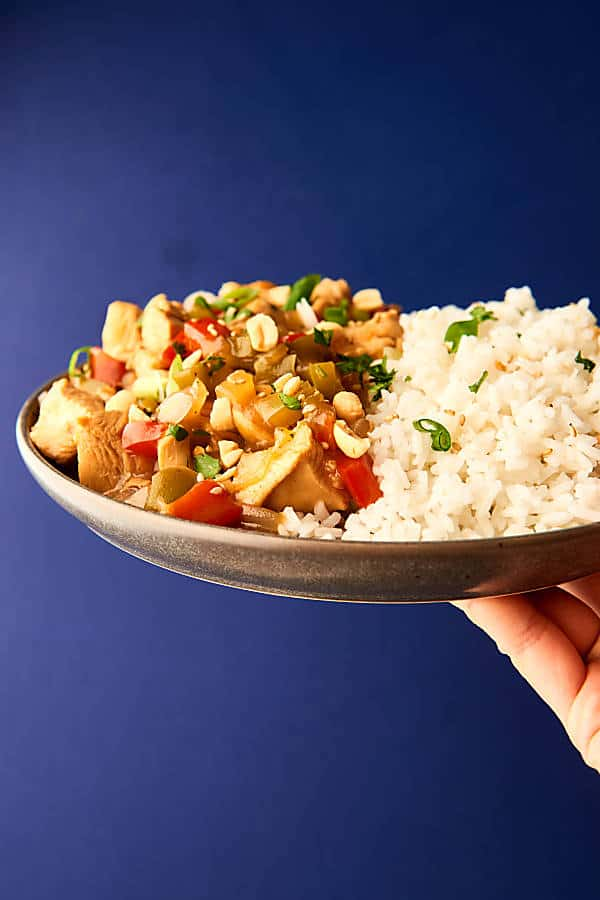 Plate of kung pao chicken and rice held blue background