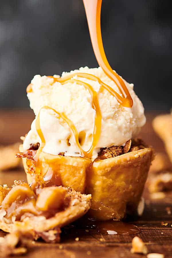 mini apple pie topped with scoop of ice cream and drizzled with caramel