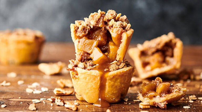 two mini apple pies stacked, others in background