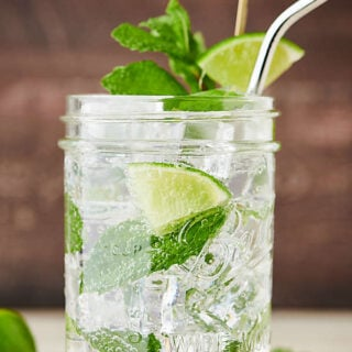 mojito in a jar with lime, mint, and straw side view