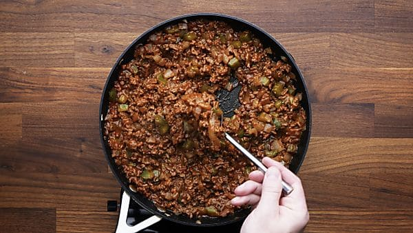 sloppy joe filling in skillet being scooped with spoon