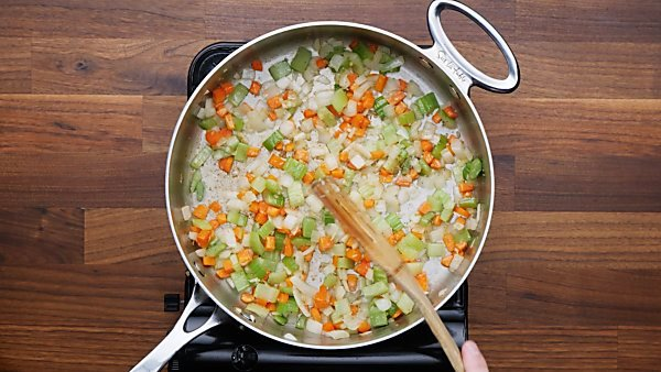 veggies and garlic being cooked in saute pan
