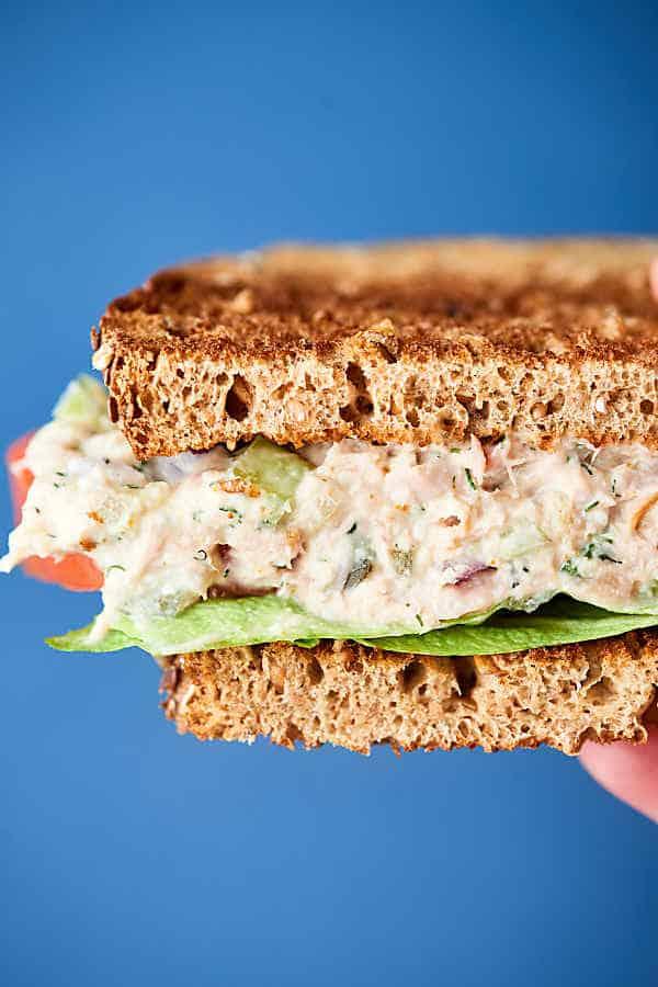 Half tuna salad sandwich held blue background