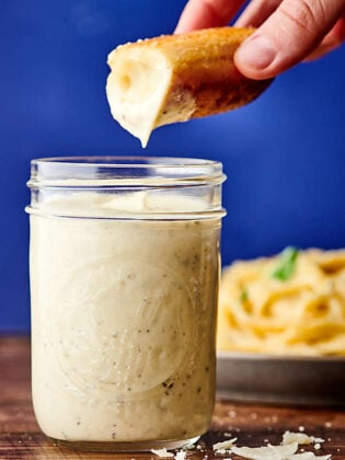 breadstick being dipped in jar of alfredo sauce