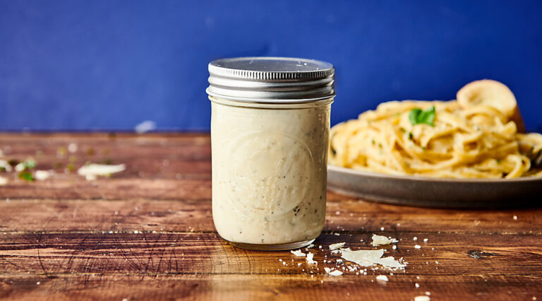 jar of alfredo sauce, plate of pasta in background