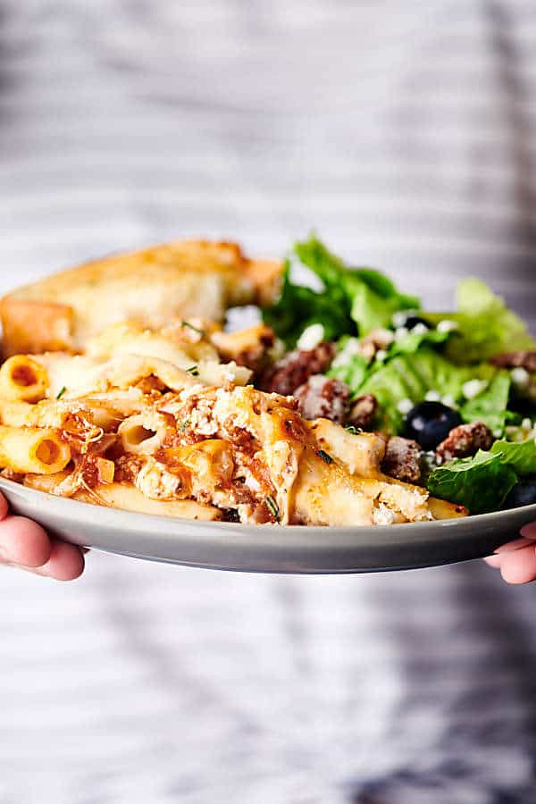 plate of baked ziti with side salad held two hands