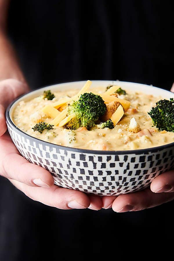 bowl of broccoli cheddar soup held two hands