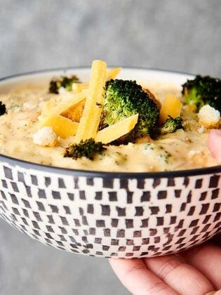 bowl of broccoli cheddar soup held
