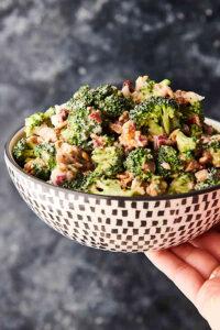 bowl of broccoli salad held