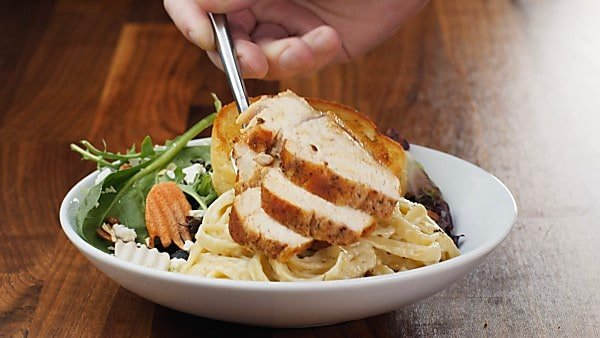 sliced chicken being put on plate with pasta