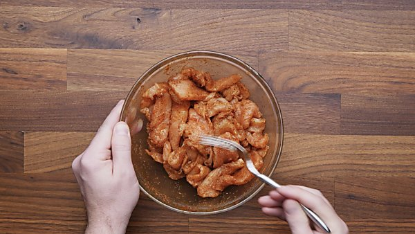 chicken with marinade in mixing bowl