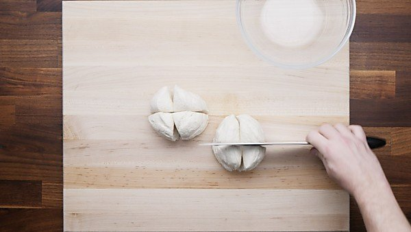 quartered biscuit dough on cutting board