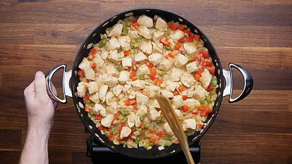 chicken and veggies being cooked in skillet