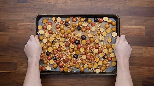 potatoes and onion tossed with spices on baking sheet