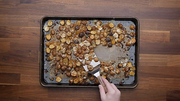 roasted potatoes sprinkled with parmesan being scooped with spatula