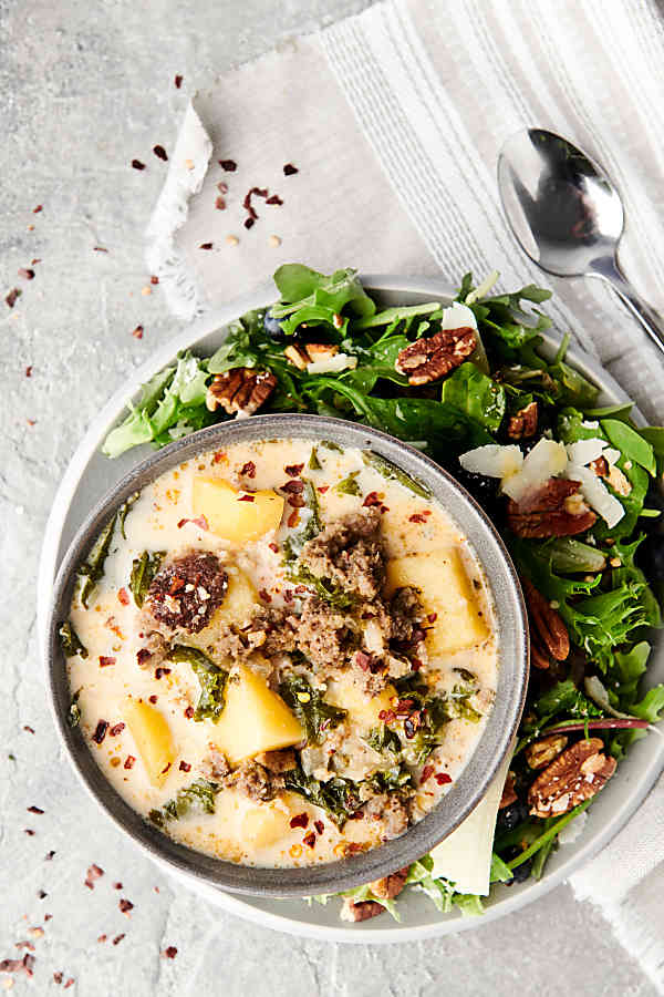 bowl of zuppa toscana on plate with salad above