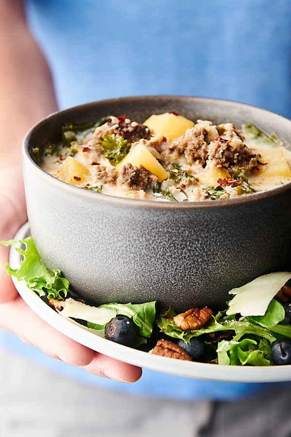 bowl of zuppa toscana on plate with salad held two hands