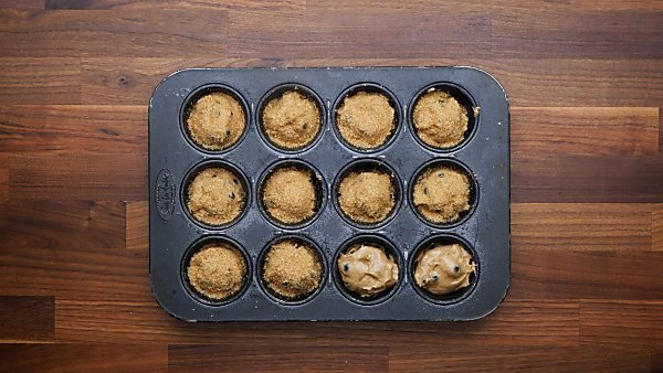 muffin batter in muffin tin sprinkled with sugar