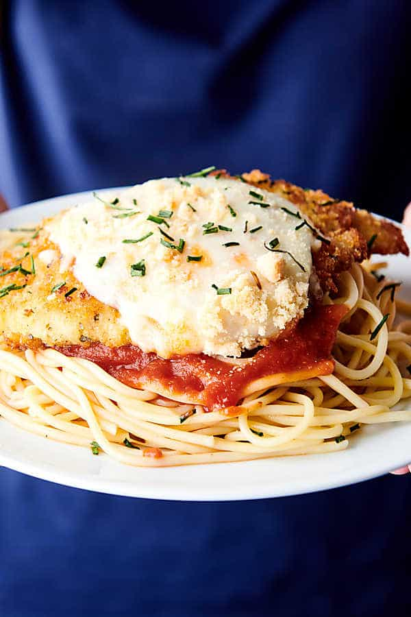 plate of chicken parmesan held two hands