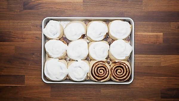 frosting spread over cinnamon rolls on baking sheet