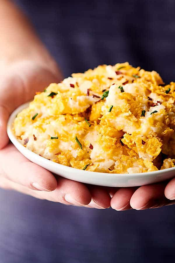 plate of hashbrown casserole held two hands