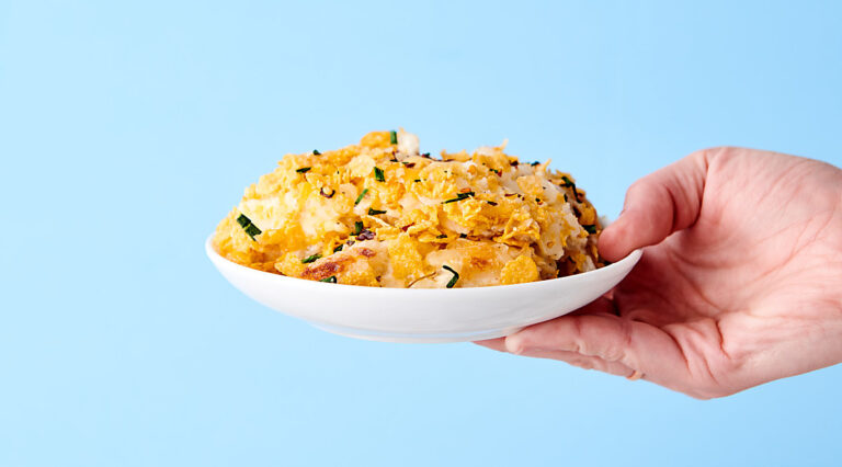 plate of hashbrown casserole held blue background