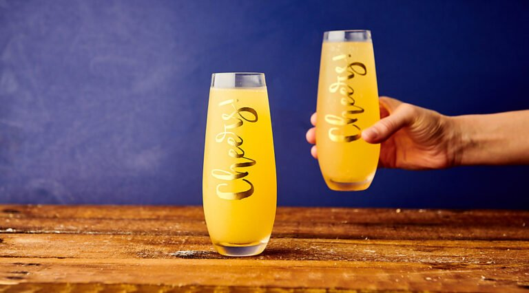 two mimosa glasses, one being picked up