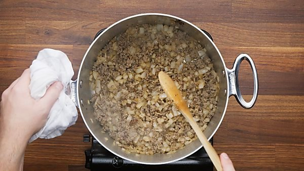 sausage, onion, and seasonings being cooked in stockpot