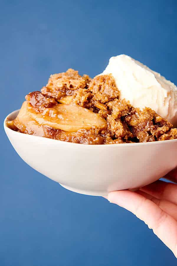 bowl of apple crumble held blue background